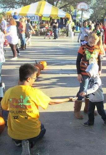 Volunteer at a Fair Helping a Child
